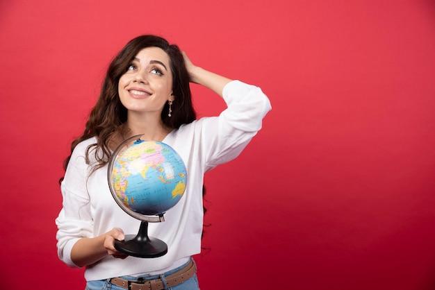 Młoda kobieta pozuje z kulą ziemską na czerwonym tle. zdjęcie wysokiej jakości