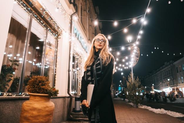 Młoda kobieta pozuje z laptopem na ulicie