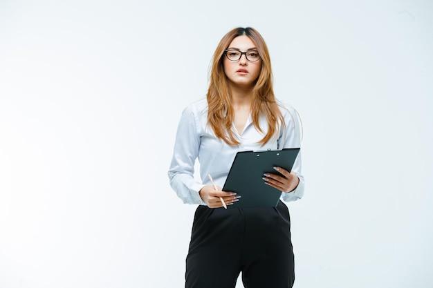 Młoda kobieta pozuje z okularami i schowkiem