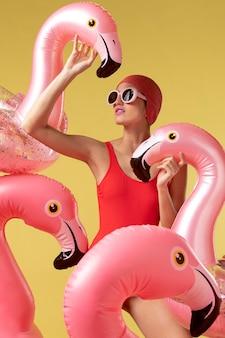 Młoda kobieta pozuje z pierścieniem pływackim flamingo