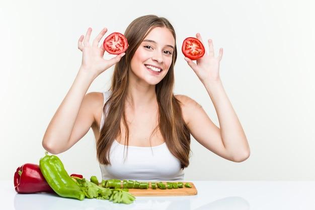 Młoda kobieta pozuje z pomidorem