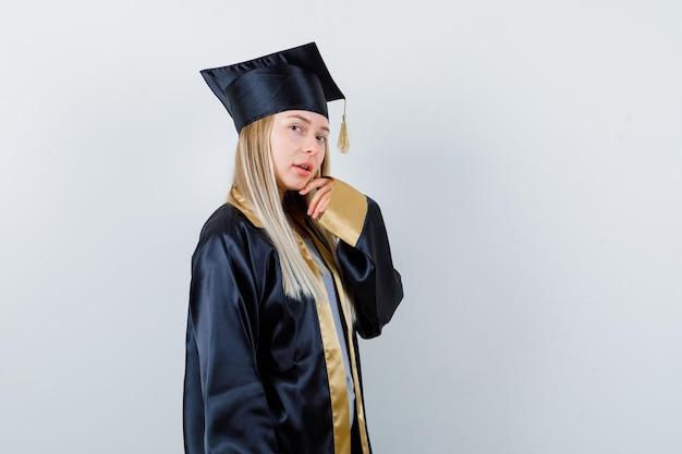 Młoda kobieta pozuje z ręką na brodzie w mundurze absolwenta i wygląda z wdziękiem