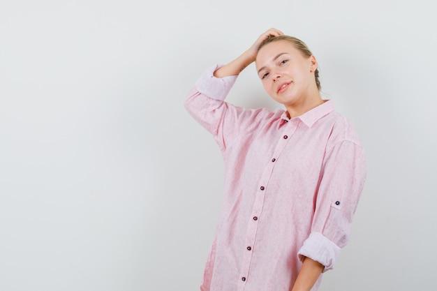 Młoda kobieta pozuje z ręką na głowie w różowej koszuli i patrząc wesoło