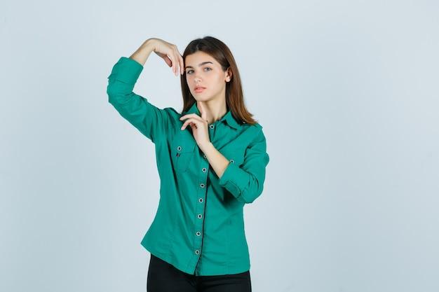 Młoda kobieta pozuje z rękami wokół głowy w zielonej koszuli i wygląda delikatnie. przedni widok.