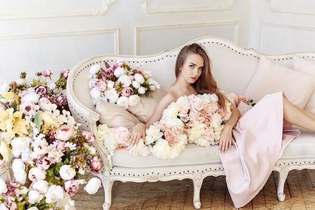 Młoda kobieta pozuje z różnymi kolorowymi kwiatami we wnętrzach studio z sofą.