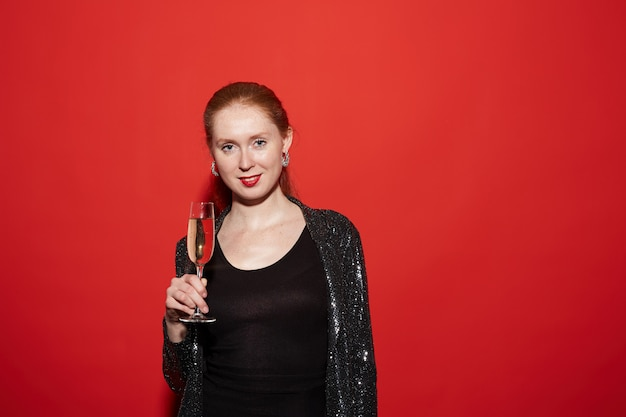 Młoda kobieta pozuje z szampanem przy przyjęciem