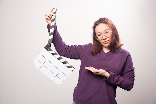 Młoda kobieta pozuje z taśmą kinową na bielu. zdjęcie wysokiej jakości