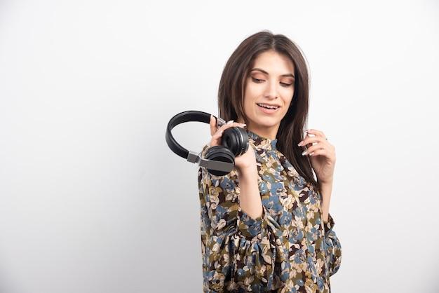 Młoda kobieta pozuje ze słuchawkami na białym tle.