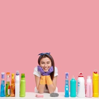 Młoda kobieta pozuje ze środkami czyszczącymi