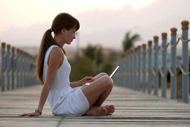 Młoda kobieta pracownik biurowy pracuje na komputerze przenośnym na zewnątrz w ciepły letni wieczór. koncepcja pracy zdalnej i nauki.