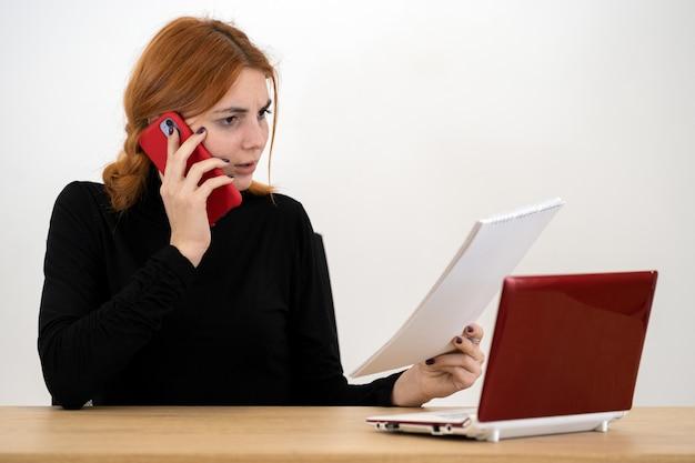 Młoda kobieta pracownik biurowy rozmawia przez telefon komórkowy siedzi za biurkiem z laptopa i notebooka.
