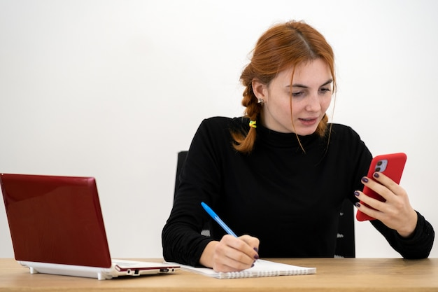 Młoda kobieta pracownik biurowy rozmawia przez telefon komórkowy siedzi za biurkiem z laptopem i notebookiem.