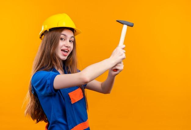 Młoda kobieta pracownik budowniczy w mundurze budowy i hełm ochronny trzymając młotek uśmiechnięty wesoło stojąc nad pomarańczową ścianą