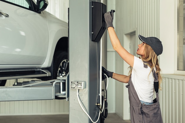 Młoda kobieta pracownik usługi podnoszenia samochodu