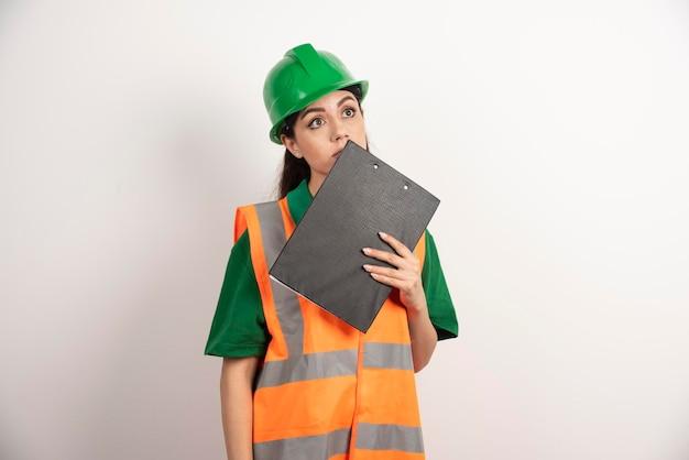 Młoda kobieta pracownika z hełmem i schowkiem. zdjęcie wysokiej jakości