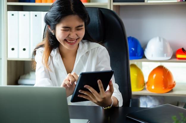 Młoda kobieta pracująca cieszy się używać pastylkę w biurze
