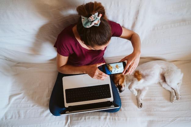 Młoda kobieta pracująca na laptopie w domu, siedząca na kanapie, robiąca zdjęcie z telefonu komórkowego swojego uroczego małego psa. koncepcja technologii i zwierząt domowych