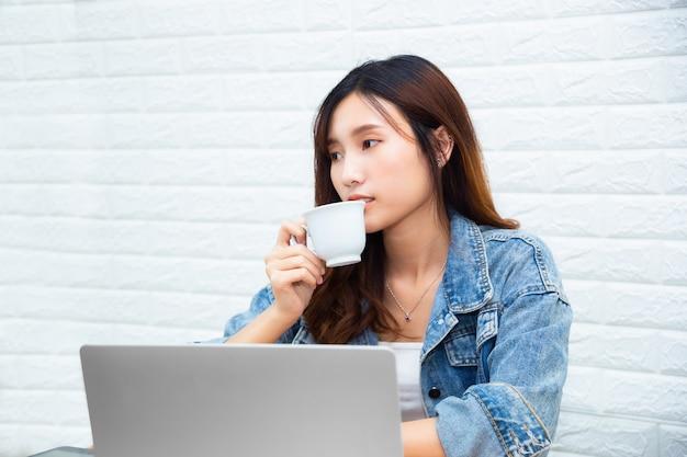 Młoda kobieta pracująca pije kawę przy biurem
