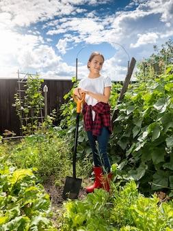 Młoda kobieta pracująca w przydomowym ogrodzie w jasny słoneczny dzień
