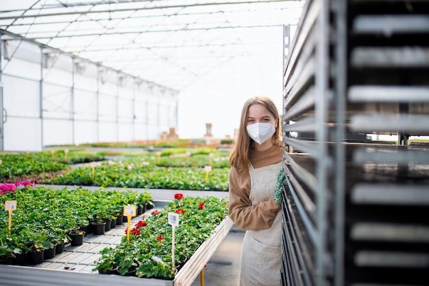 Młoda kobieta pracująca w szklarni w centrum ogrodniczym, koncepcja koronawirusa.