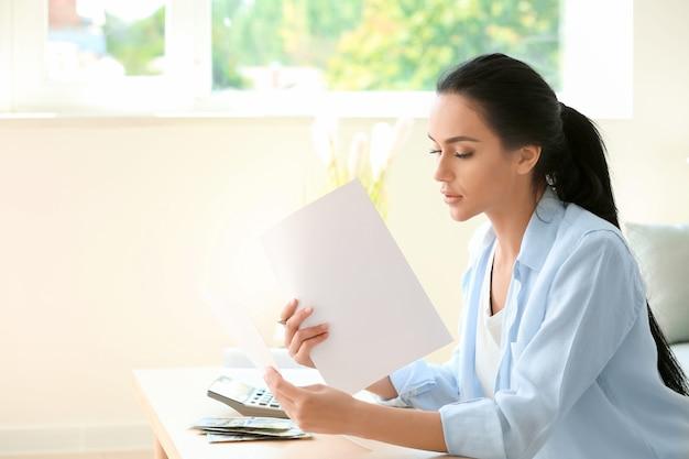 Młoda kobieta pracująca z dokumentami finansowymi przy stole