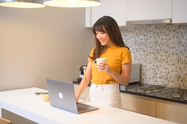 Młoda kobieta pracująca z laptopem i przy filiżance kawy, styl życia i koncepcja biznesowa