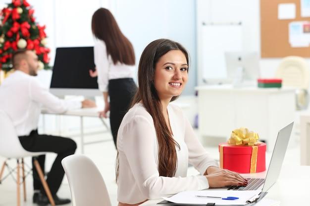 Młoda kobieta pracująca z laptopem w biurze udekorowana na boże narodzenie