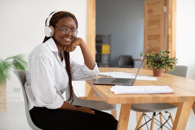 Młoda kobieta pracująca z włączonymi słuchawkami