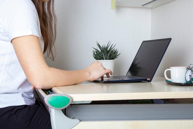 Młoda kobieta pracuje dla laptopu od domu na białym biurku. dziewczyna używa przenośnego komputer dla pisać na klawiaturze przy jej biurem na lekkim tle