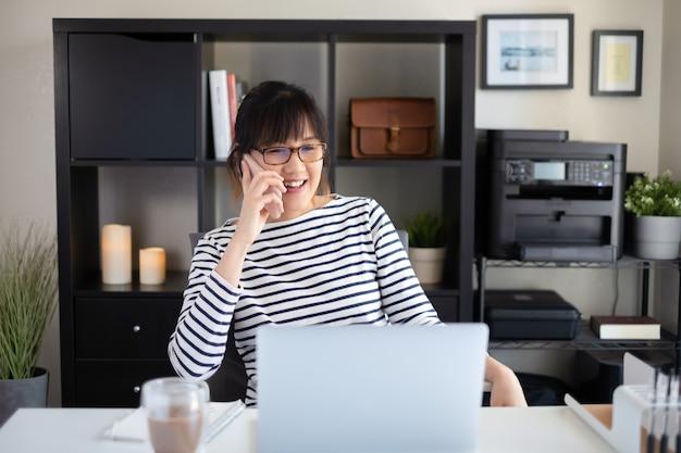 Młoda kobieta pracuje i uczy się w domu przy użyciu telefonu komórkowego podczas rozmowy i połączenia wideo.
