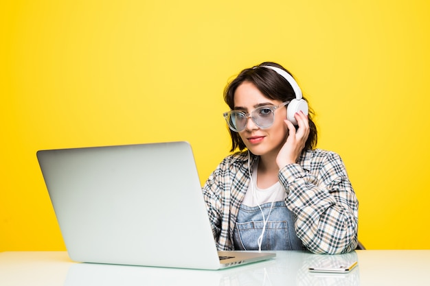 Młoda kobieta pracuje na biurku z laptopem na białym tle