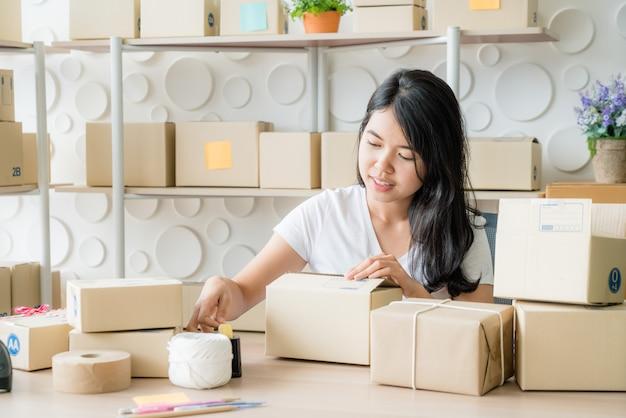 Młoda kobieta pracuje na doręczeniowej usługa przy biurem