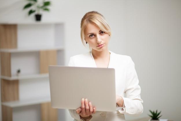Młoda kobieta pracuje na kolanach w biurze.