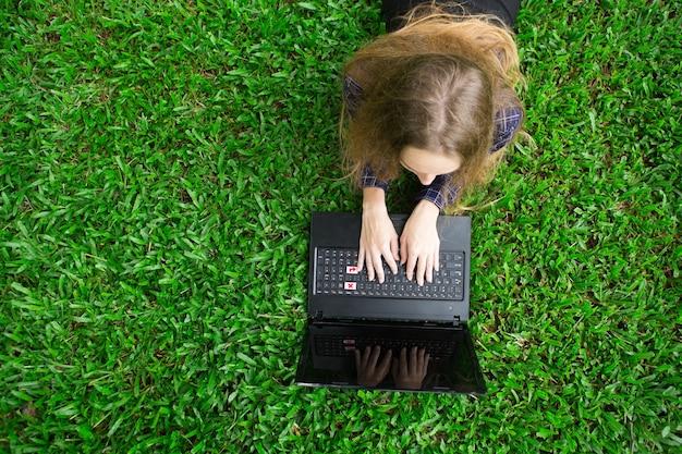 Młoda kobieta pracuje na komputerze przenośnym na trawie