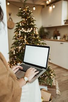 Młoda kobieta pracuje na komputerze przenośnym z pustym ekranem wyświetlacza z miejsca na kopię. nowoczesny wystrój wnętrz salonu domu udekorowany na boże narodzenie z choinką.