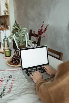 Młoda kobieta pracuje na komputerze przenośnym z pustym ekranem wyświetlacza z miejsca na kopię. wnętrze kuchni ze stołem