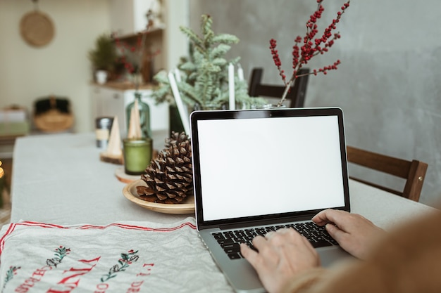 Młoda kobieta pracuje na komputerze przenośnym z pustym ekranem wyświetlacza z miejsca na kopię.