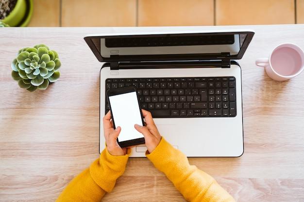 Młoda kobieta pracuje na laptopie i telefonie komórkowym w domu. praca w domu