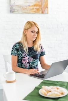 Młoda kobieta pracuje na laptopie nad biurkiem