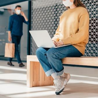 Młoda kobieta pracuje na laptopie, siedząc przed budynkiem miasta