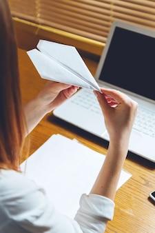 Młoda kobieta pracuje na laptopie siedząc w miejscu pracy