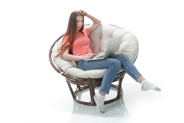 Młoda kobieta pracuje na laptopie, siedząc w wygodnym fotelu