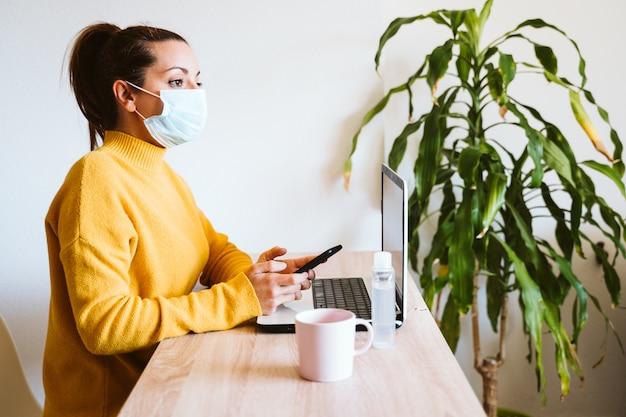 Młoda kobieta pracuje na laptopie w domu, nosząc maskę ochronną. pracuj z domu, bądź bezpieczny podczas koronawirusa covid-2019 concpt