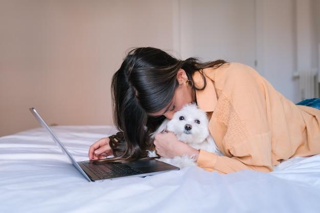 Młoda kobieta pracuje na laptopie w domu. poza tym słodki pies maltański