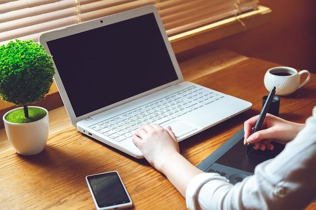 Młoda kobieta pracuje na laptopie za pomocą tabletu graficznego