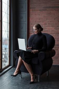 Młoda kobieta pracuje na laptopie