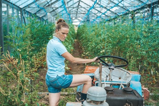 Młoda kobieta pracuje na traktorze w szklarni