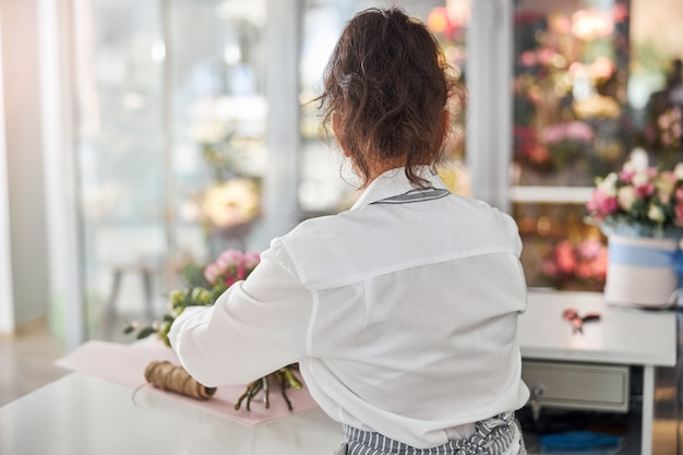 Młoda kobieta pracuje nad zrobieniem bukietu w swoim studio kwiatowym