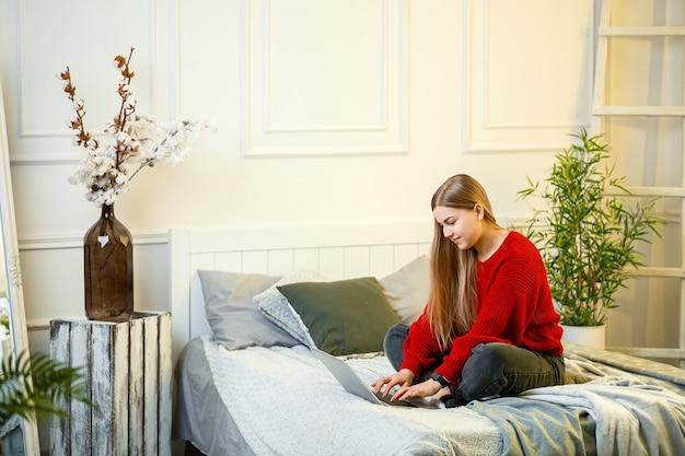 Młoda kobieta pracuje przy komputerze, siedząc na łóżku, pracując na odległość. dziewczyna z długimi włosami w czerwonym swetrze i dżinsach pracuje w domu.