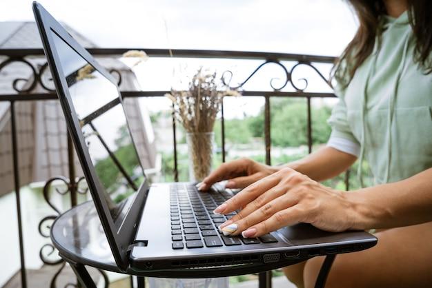Młoda kobieta pracuje przy laptopie na tarasie koncepcji pracy zdalnej